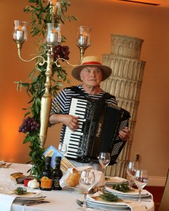Henry Edwardo playing an accordian entertaining guests at a dinner event in pittsburgh